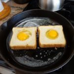 Cast iron skillet cooking egg on toast