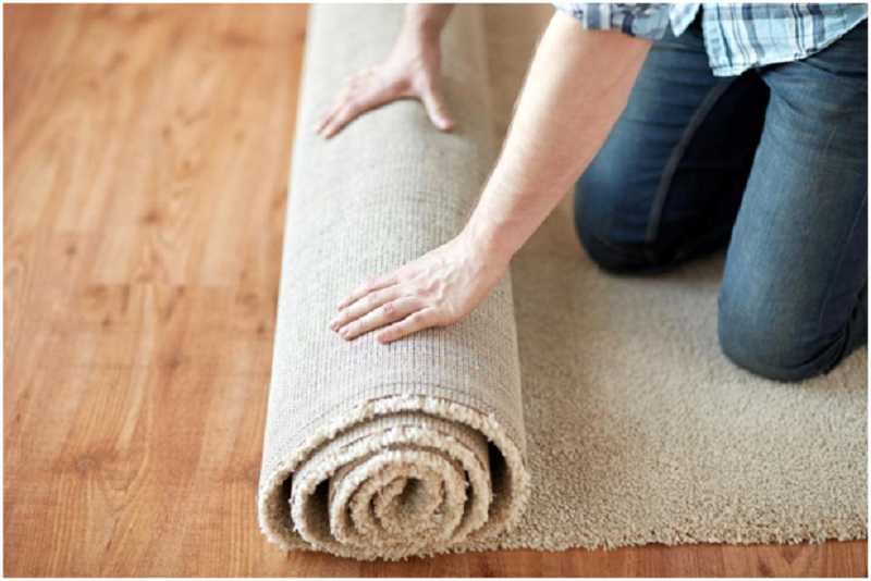 A girl unrolling a floor carpet.