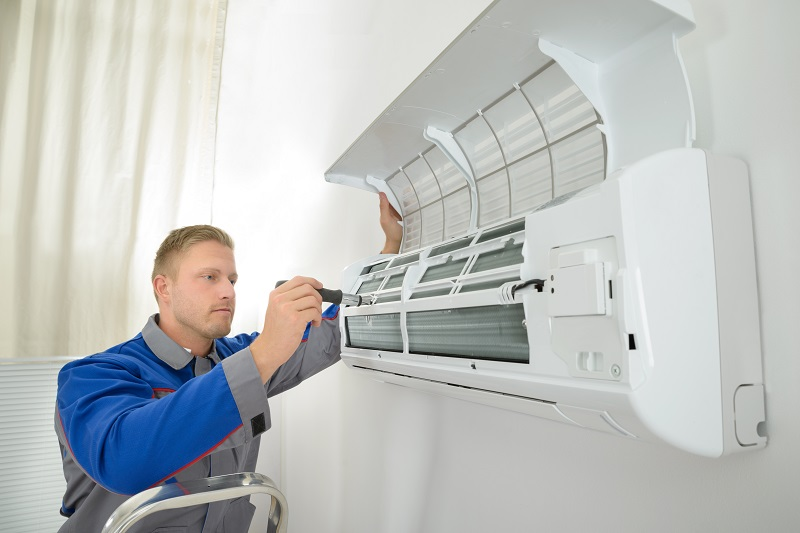 A man cleaning the air conditioner coils.