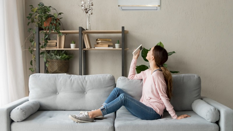 A girl turning on her air conditioner.