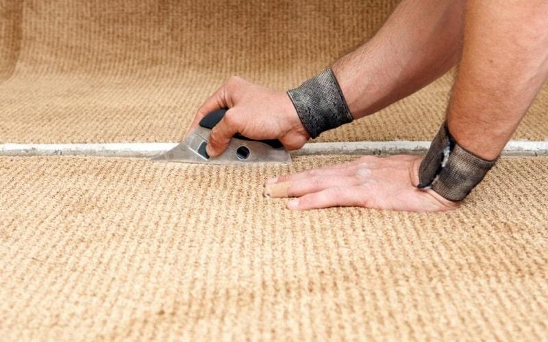 Trimming/cutting a carpet using a cutter or a carpet knife.
