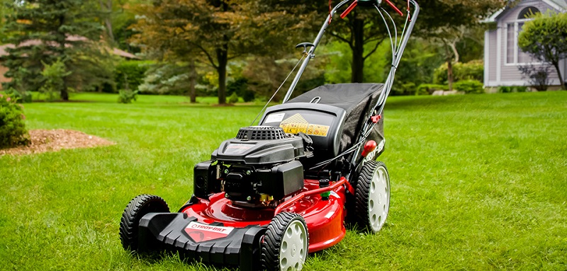 A new shiny lawn mower on the grass field.