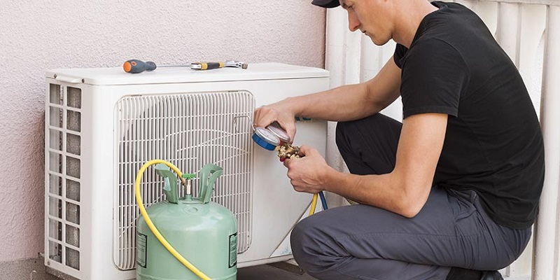 A guy checking the air conditioner refrigerant.