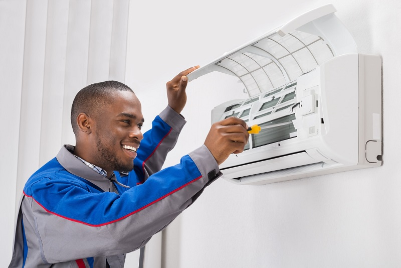 A handyman doing air conditioner check up.