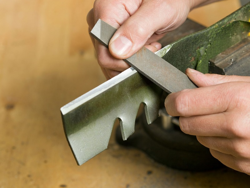 A metal file can be used the sharpen the mower blade without removing it.