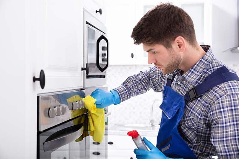 Man cleaning oven door