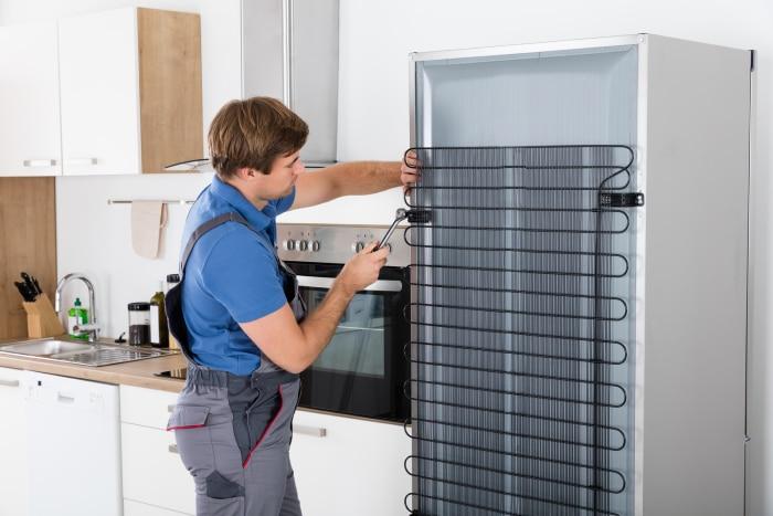 male technician repairing refrigerator