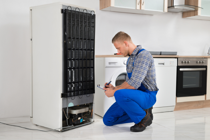 Male Technician checking the back of a refrigerator