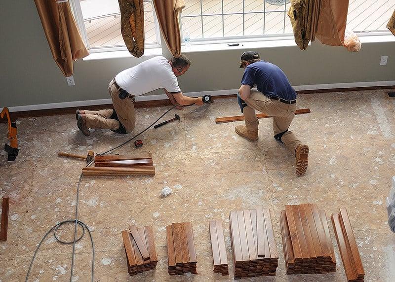 Contractors installing hardwood floor underlayment