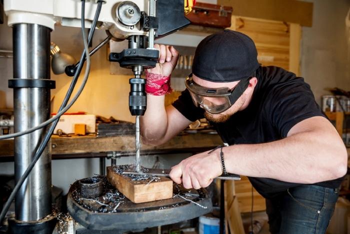 man using a floor drill press