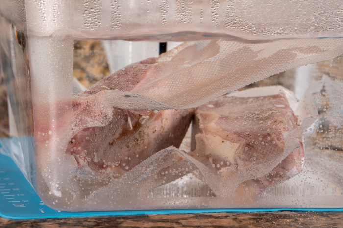 vacuum-sealed meat submerged in water for sous vide