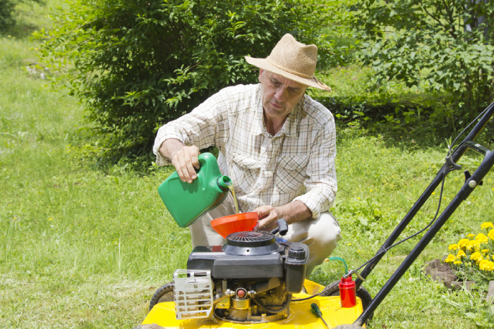 male pouring oil into lawn mower