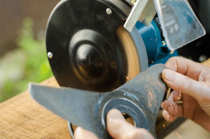 male sharpening lawn mower blade
