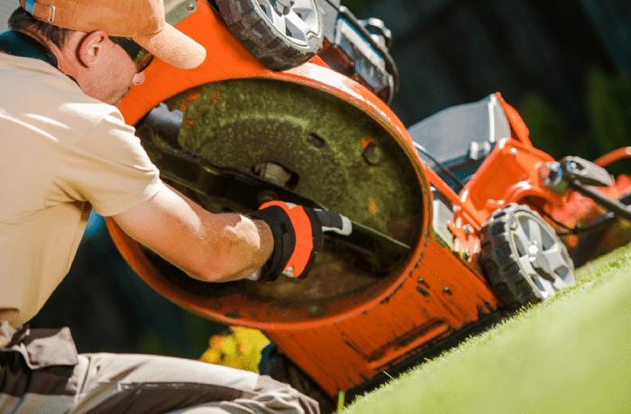 male checking lawn mower blades