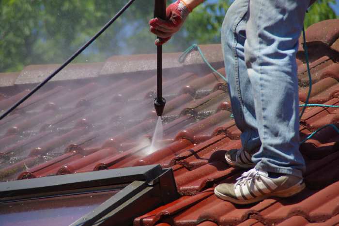 male using pressure washer to clean roof