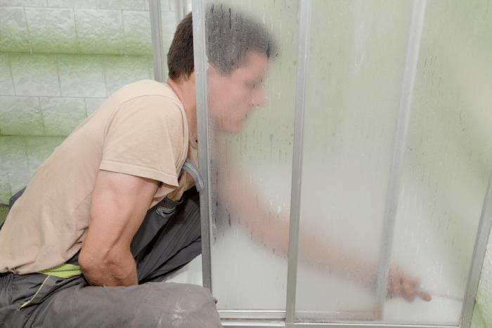 male checking sliding shower door