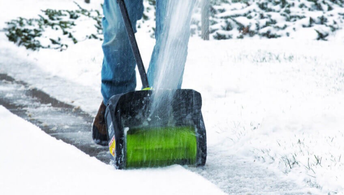 male using a Snow blower for clearing path way