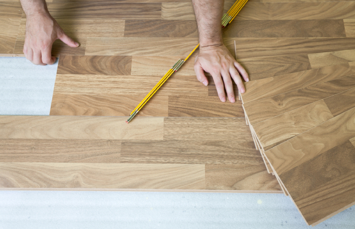 male laying down laminate on floor