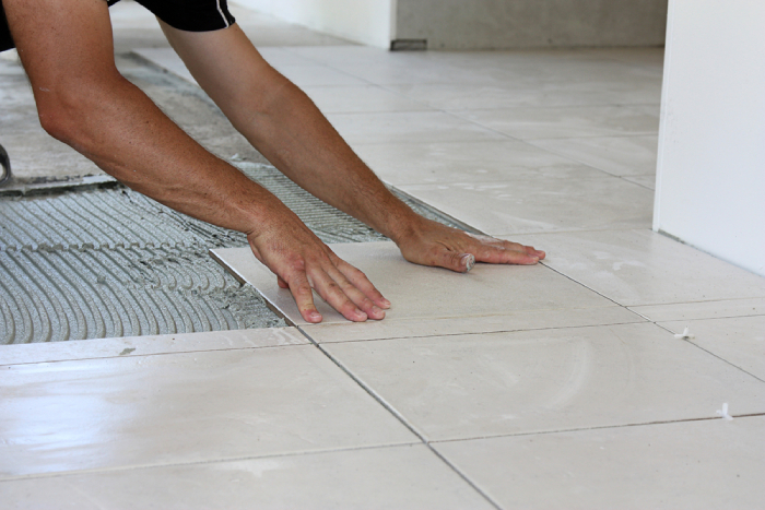 male laying down tiles