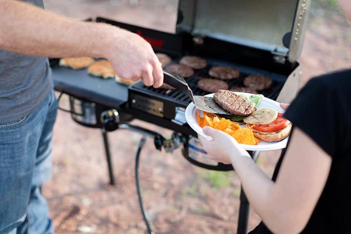 Male cooking burgers and putting it to a plate