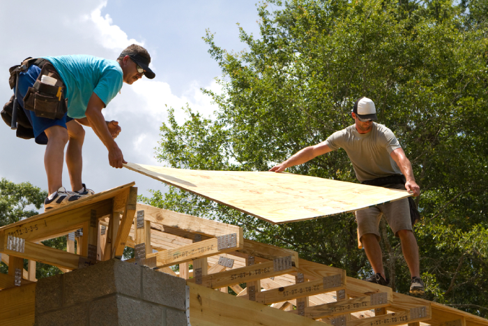 two male holding a plyboard on a rooftop
