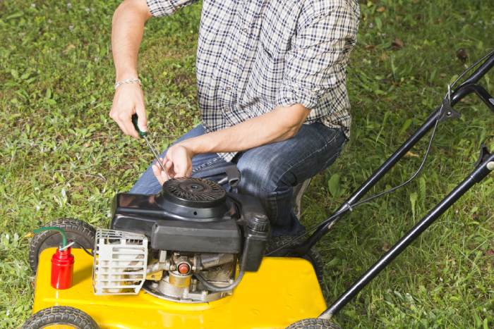 male fixing a yellow lawn mower