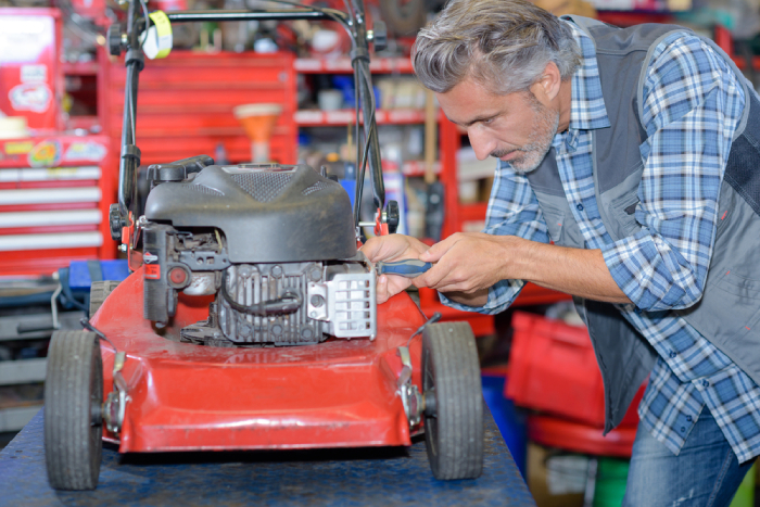 male fixing a lawn mower on a table