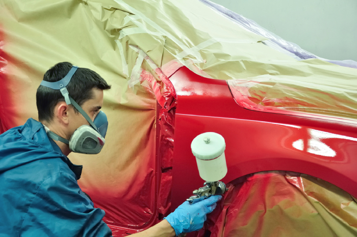 male spraying red paint on a car