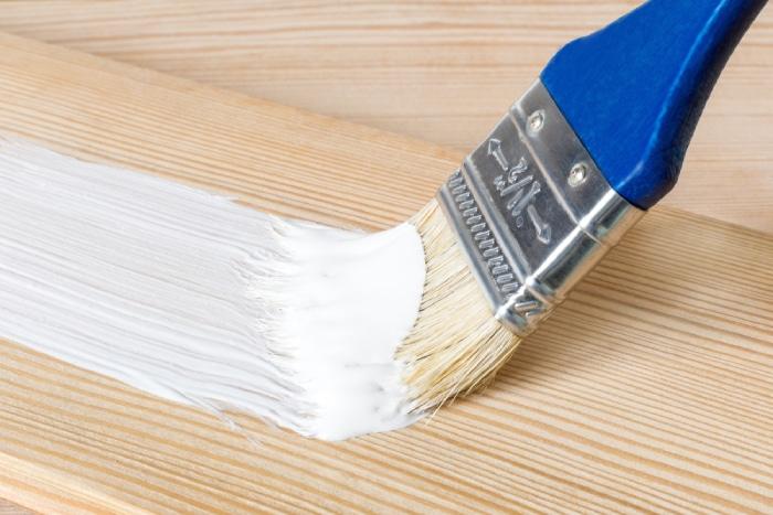 Brush painting white paint over wood