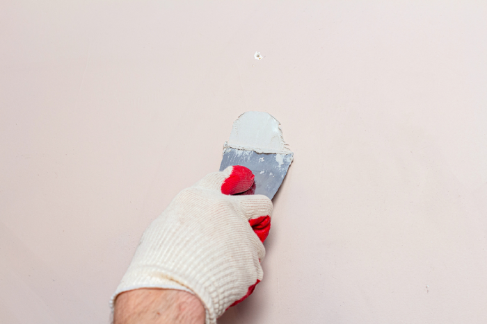 hand filling holes and cracks on the wall