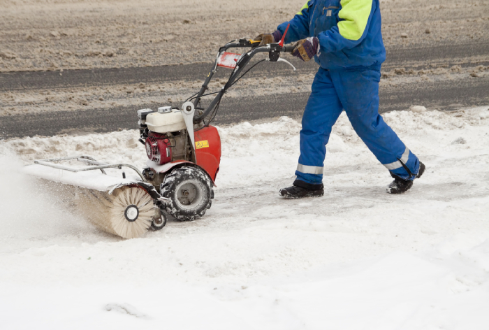 male using a snow blower