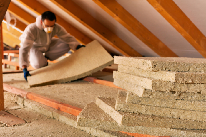 male installing insulation in the attic