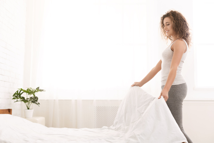 female changing bed sheets