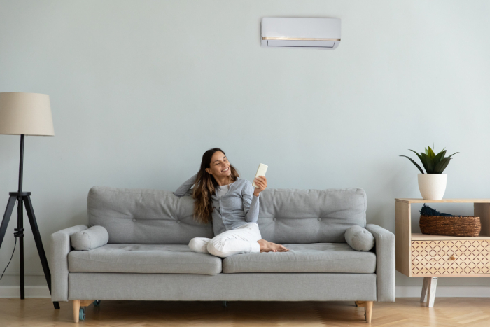 female holding an air conditioner remote