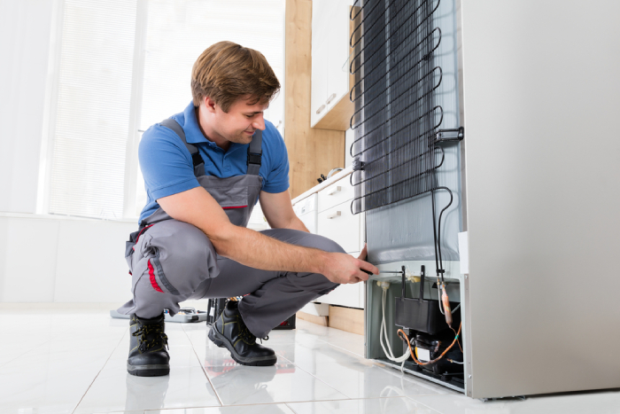 technician checking the back of refrigerator