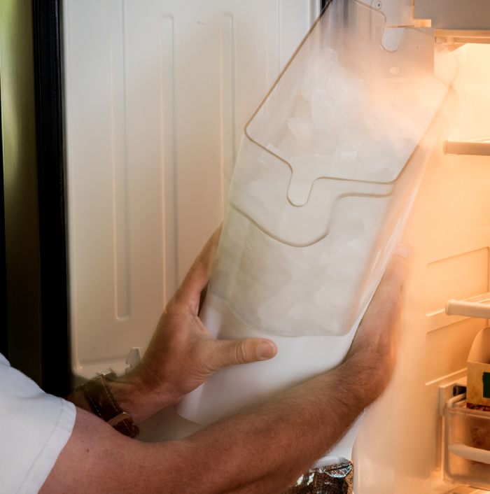male removing ice maker tub