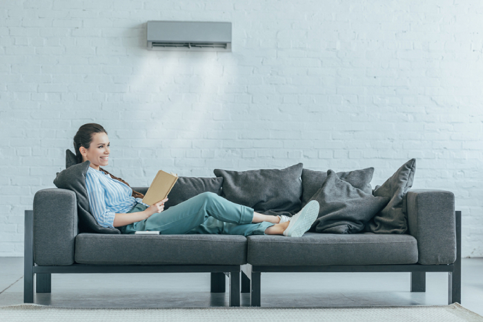 female relaxing on a couch with clear view of AC