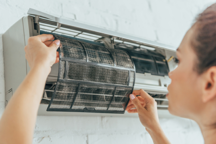 female checking the air filter of AC