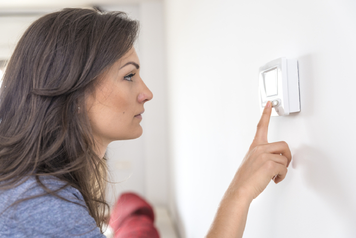 female checking thermostat