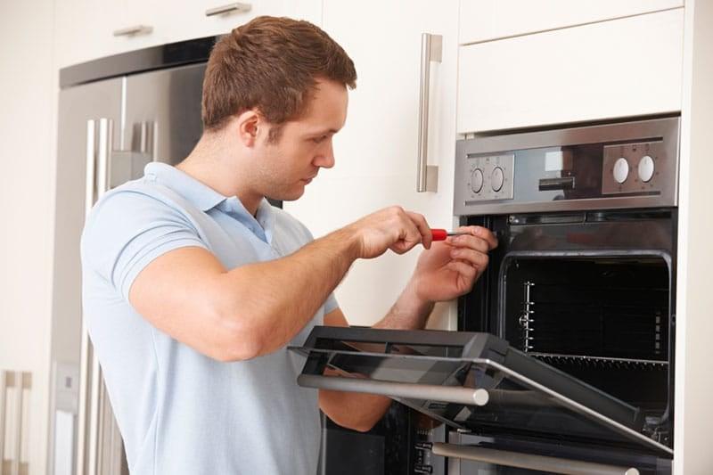 Repairman working on oven