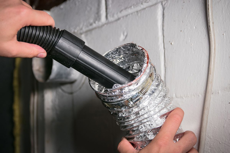Cleaning the dryer vent duct with a vacuum.