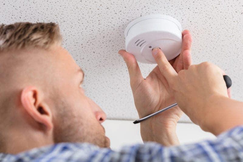 Man pressing button on smoke alarm